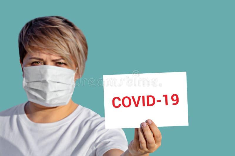 Vrouw in gezichtsmasker houdt leeg met het opschrift COVID-19 royalty-vrije stock foto