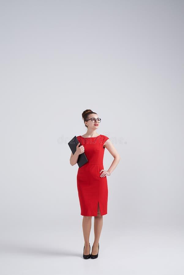 Vrouw in glazen die omslag houden en aan het recht kijken stock foto