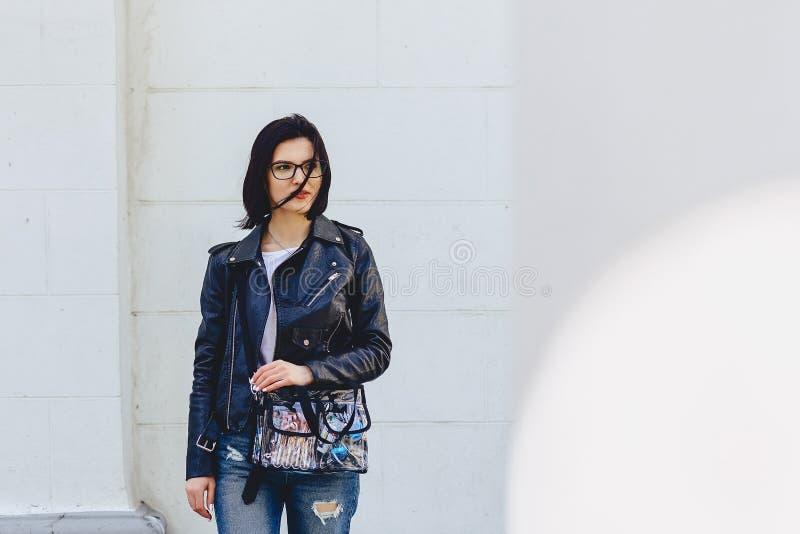 Vrouw in glazen in leerjasje op straat stock foto's
