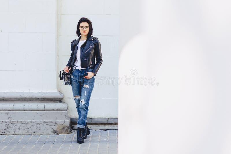 Vrouw in glazen in leerjasje op straat stock fotografie