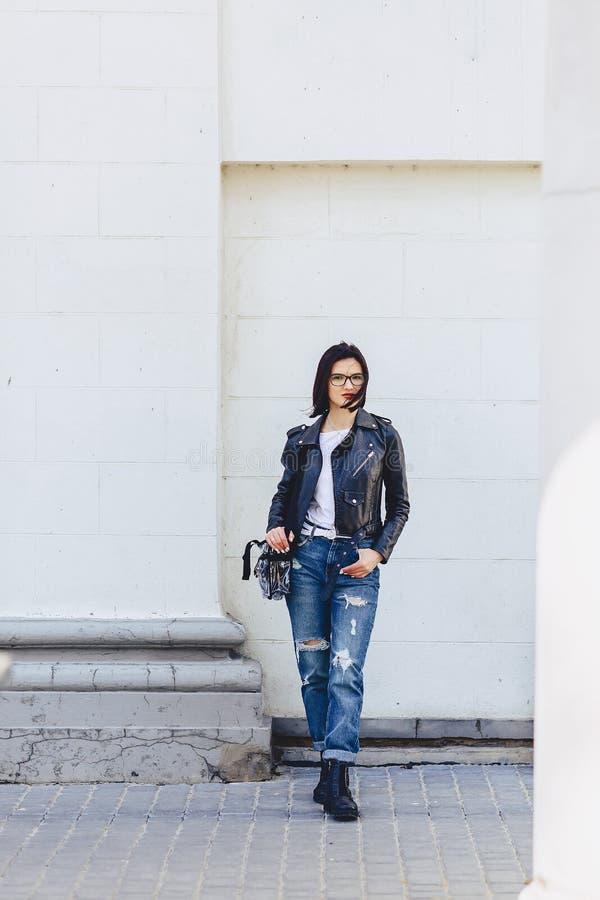 Vrouw in glazen in leerjasje op straat royalty-vrije stock afbeeldingen