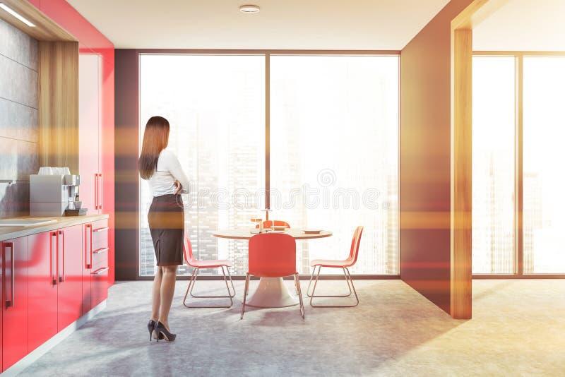 Vrouw in grijze en rode keuken stock afbeelding