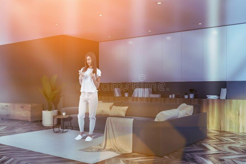 Vrouw in grijze en witte woonkamer met bank stock afbeeldingen