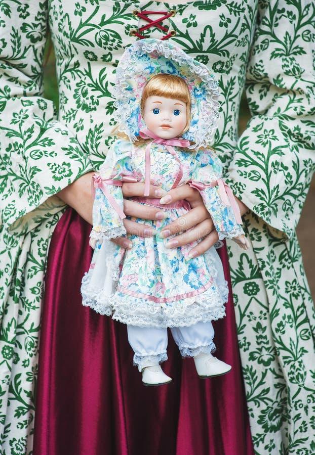 Vrouw in groene middeleeuwse kleding met uitstekende porseleinpop royalty-vrije stock afbeelding