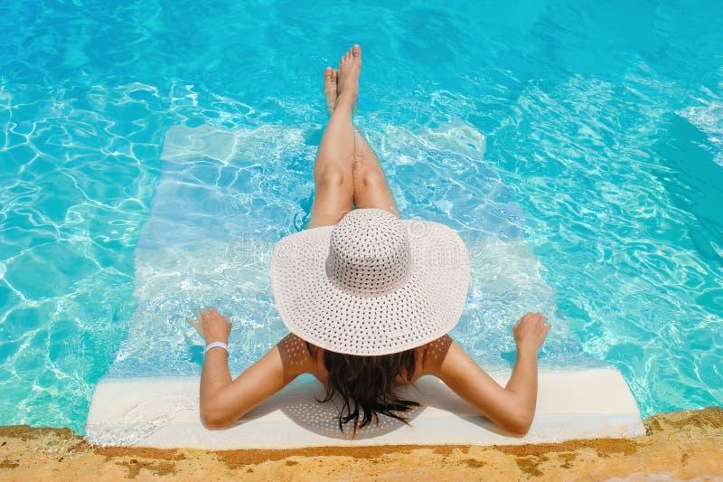 Vrouw in grote hoed die op lanterfanter door de pool liggen stock foto's