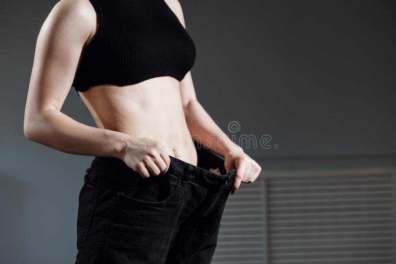 Vrouw in grote jeans, vermageringsdieet, geschiktheid stock fotografie