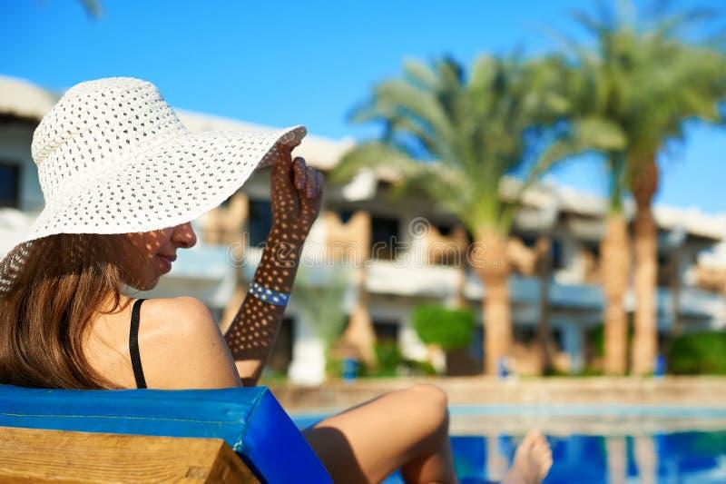 Vrouw in grote witte hoed die op een lanterfanter dichtbij het zwembad bij het hotel, de tijd van de conceptenzomer liggen om in  royalty-vrije stock foto's