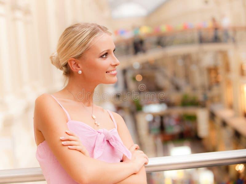 Vrouw in grote zaal bij leuning stock foto