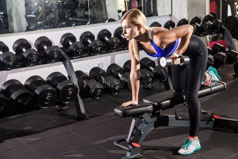 Vrouw in gymnastiek over domoortraining die wordt gebogen royalty-vrije stock afbeeldingen
