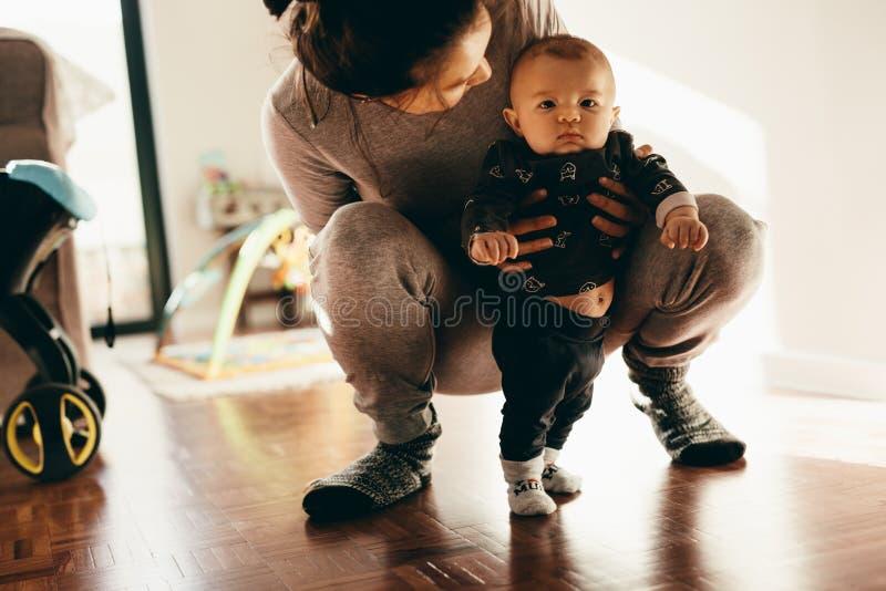 Vrouw haar baby houden die hurkend op vloer stock afbeelding