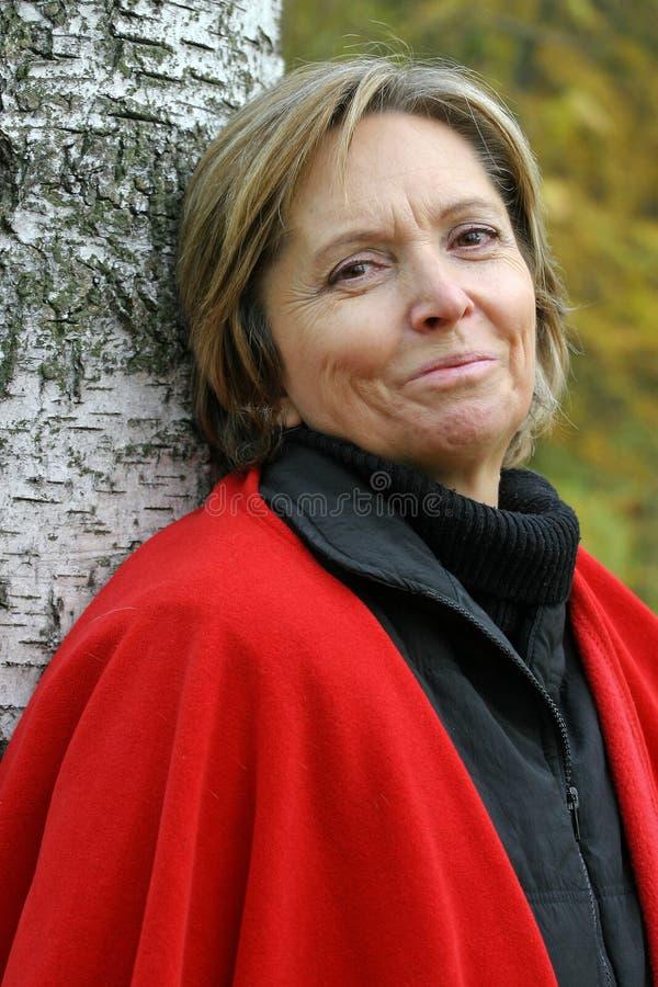 Vrouw in haar jaren '50 die zich door de boom bevinden stock afbeeldingen