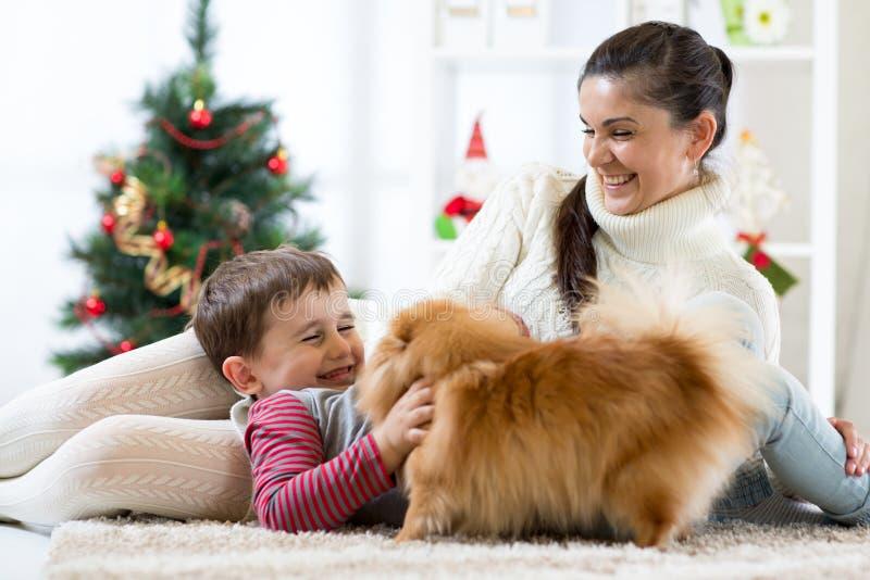Vrouw, haar zoon en hond die in geknuffel in Kerstmistijd genieten van royalty-vrije stock foto's