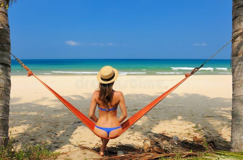 Vrouw in hangmat op strand stock foto's