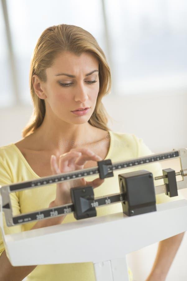 Vrouw het Aanpassen Gewichtsschaal bij Gezondheidsclub stock foto