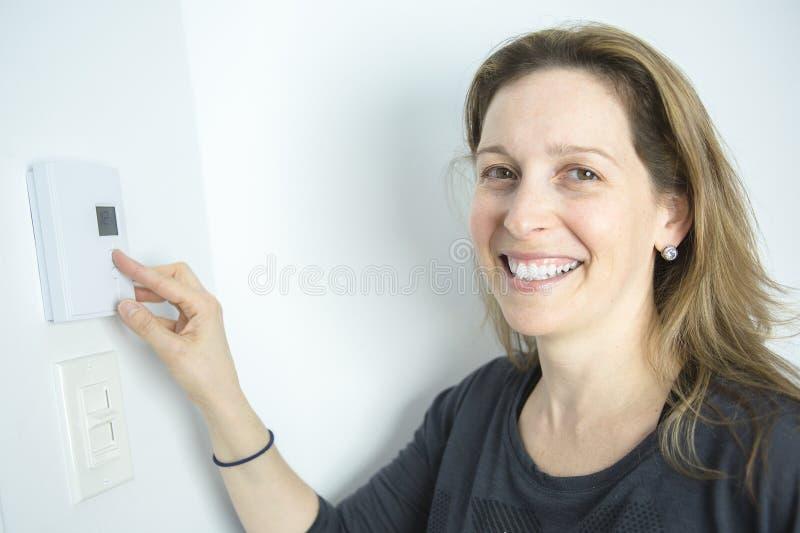 Vrouw het Aanpassen Thermostaat op Huis Verwarmingssysteem royalty-vrije stock foto