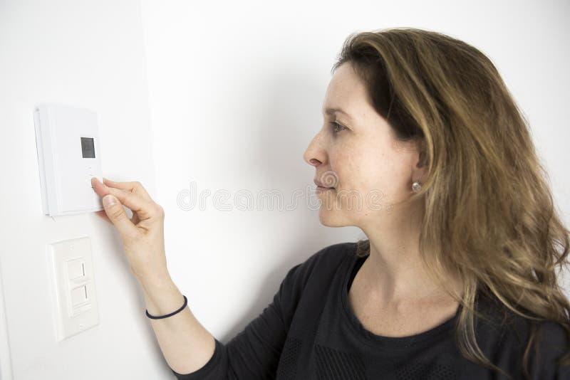 Vrouw het Aanpassen Thermostaat op Huis Verwarmingssysteem royalty-vrije stock afbeeldingen