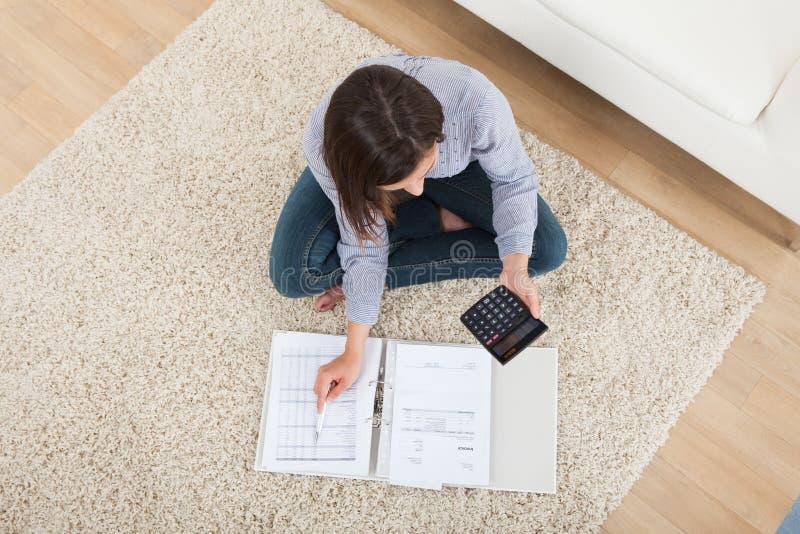 Vrouw het berekenen huisfinanciën op deken stock afbeelding
