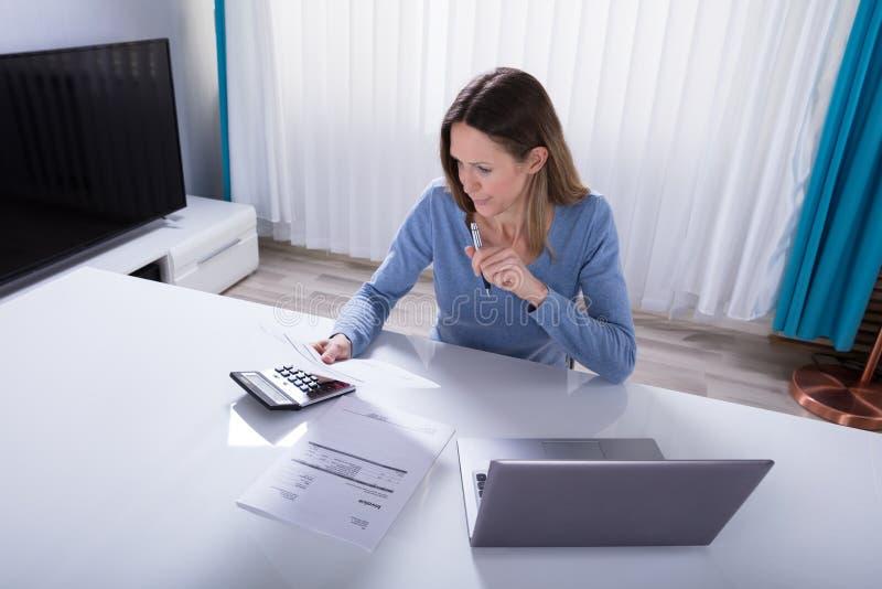 Vrouw het Berekenen Rekening met Calculator thuis royalty-vrije stock foto's