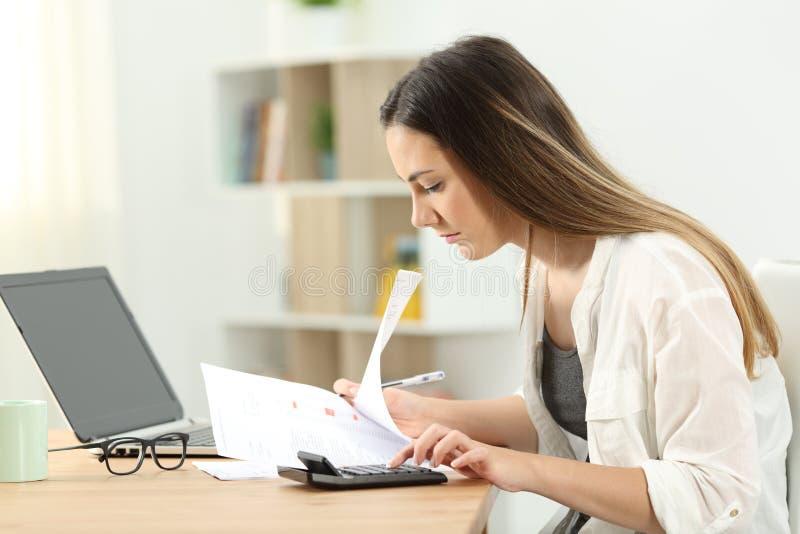 Vrouw het berekenen uitgaven thuis stock afbeelding