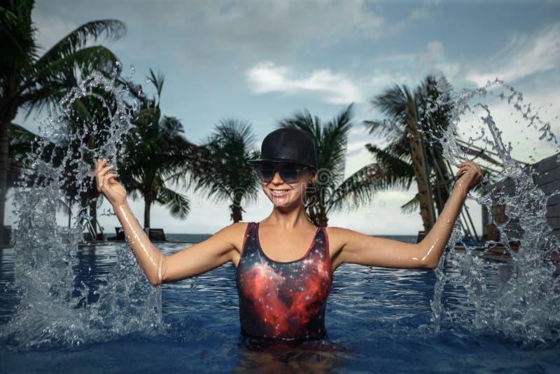 Vrouw het bespatten in het blauwe zwemmen stock foto's