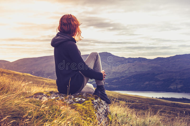 Vrouw het bewonderen zonsondergang vanaf bergbovenkant royalty-vrije stock afbeeldingen
