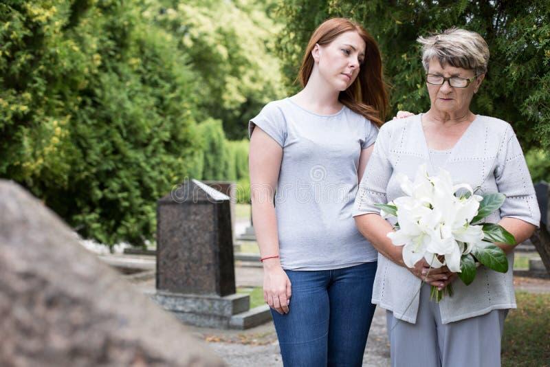 Vrouw het bezoeken graf van echtgenoot stock foto