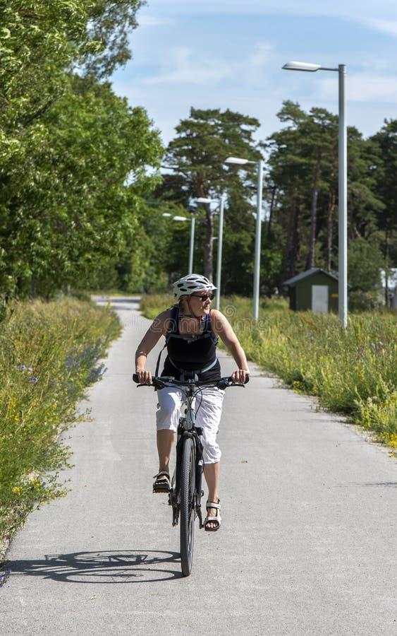 Vrouw het bicycling op de weg stock afbeeldingen