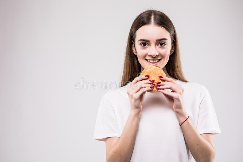 Vrouw het bijten hamburger geïsoleerd portret op grijze achtergrond Het concept van de gezondheid stock fotografie