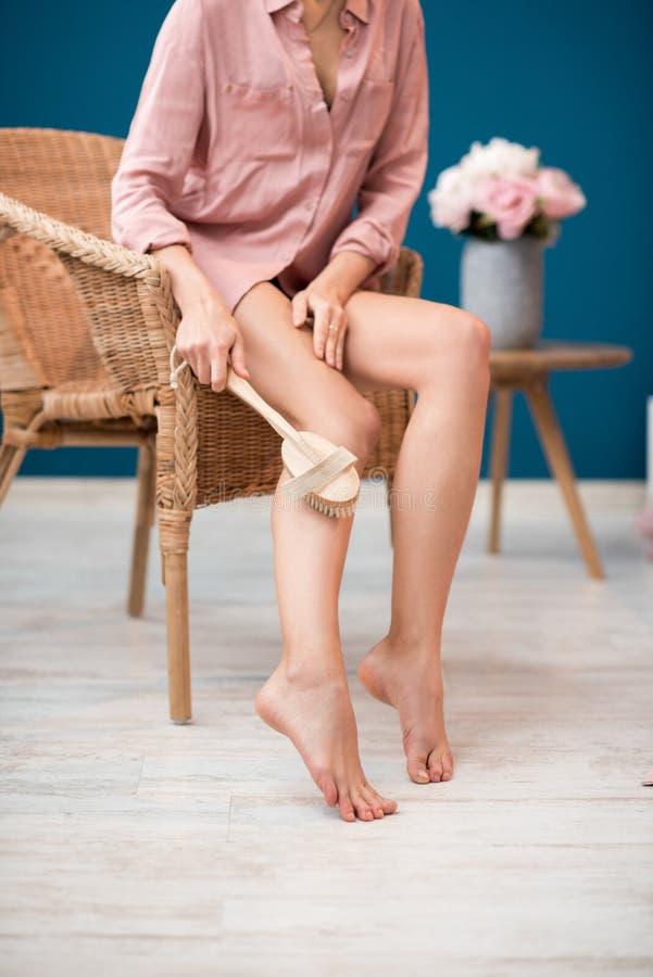 Vrouw het borstelen benen thuis royalty-vrije stock fotografie