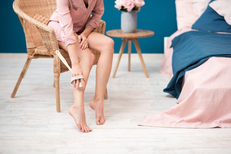 Vrouw het borstelen benen thuis stock fotografie