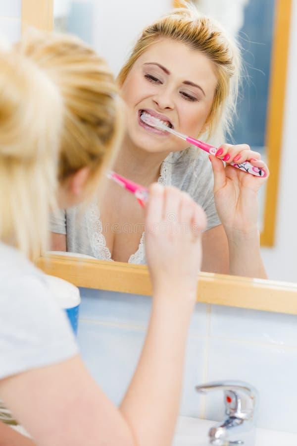Vrouw het borstelen schoonmakende tanden in badkamers stock afbeeldingen