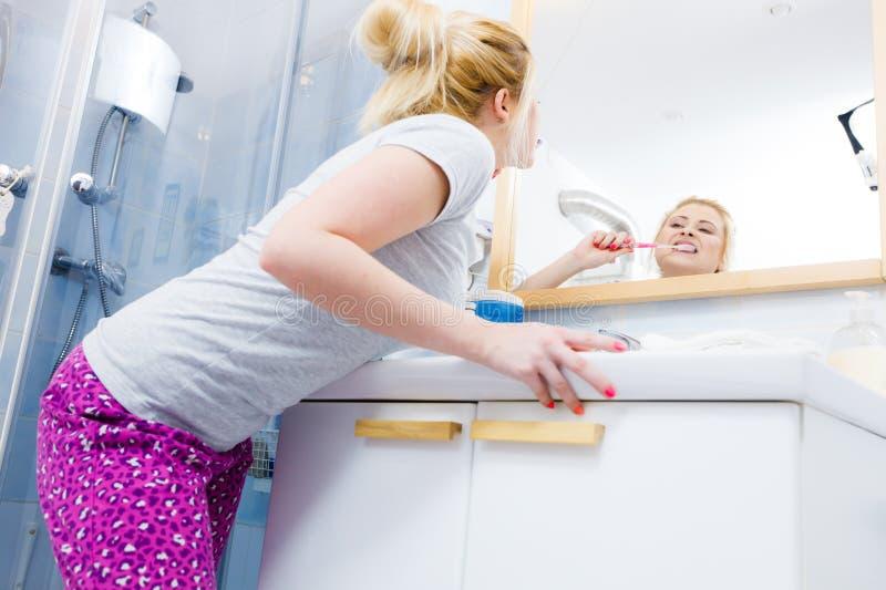 Vrouw het borstelen schoonmakende tanden in badkamers royalty-vrije stock fotografie