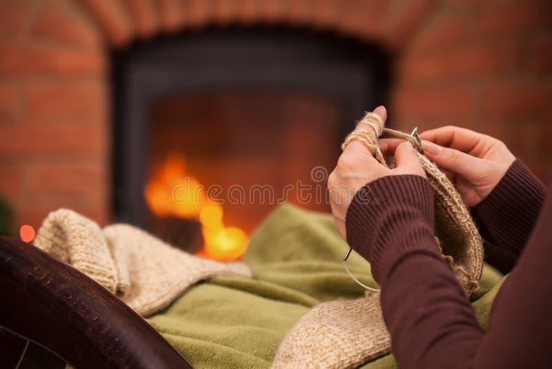 Vrouw het breien door de open haard - close-up op handen royalty-vrije stock fotografie