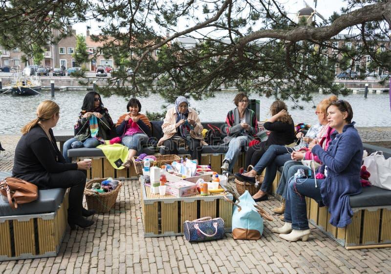 Vrouw het breien op een bank buiten op multiculturedag in Holland royalty-vrije stock foto's
