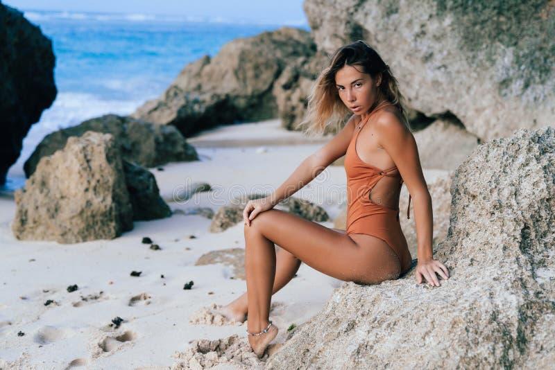 vrouw in het bruine zwempak stellen op zandig strand met grote stenen op achtergrond royalty-vrije stock afbeelding