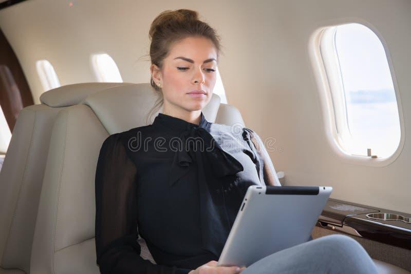 Vrouw in het collectieve straal looging bij tabletcomputer royalty-vrije stock afbeeldingen