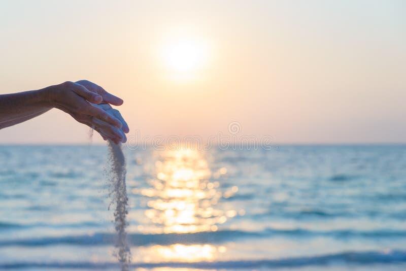 Vrouw het dalen zandkorrels van handen die yogaoefening, romantische hemel bij zonsondergang, zijaanzicht, gouden zonlicht, echte royalty-vrije stock afbeeldingen