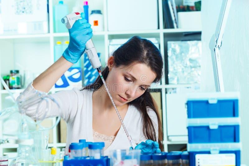 Vrouw in het de microbiologielaboratorium royalty-vrije stock afbeelding