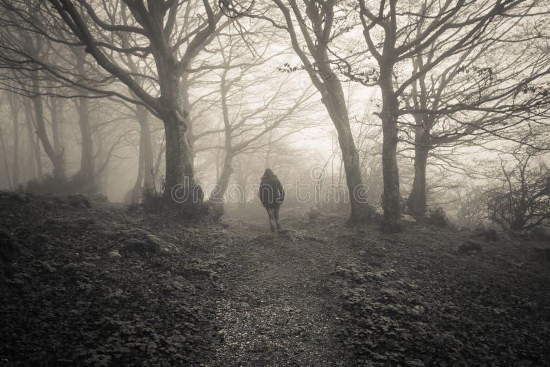 Vrouw in het donkere bos wordt verloren dat stock fotografie