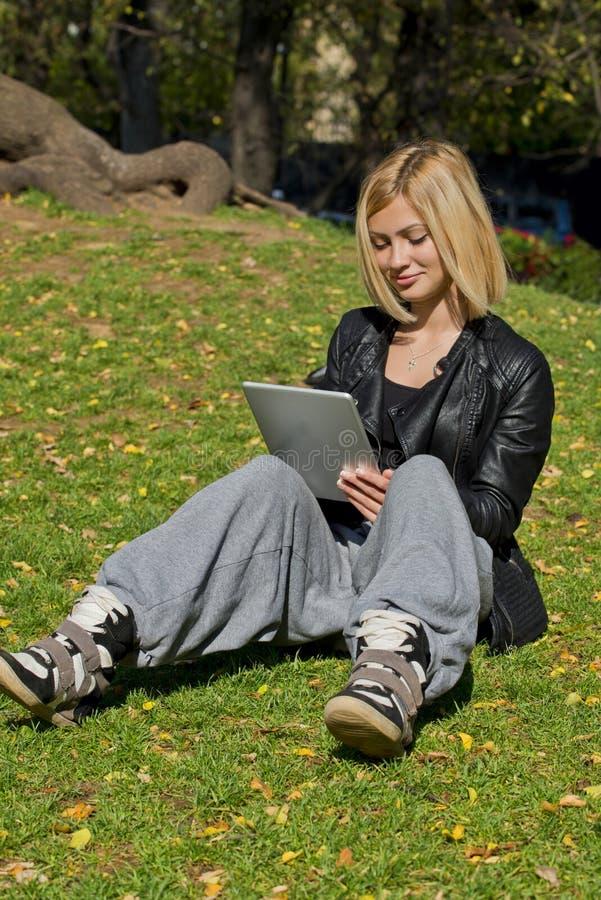 Vrouw het doorbladeren tablet in het park royalty-vrije stock foto