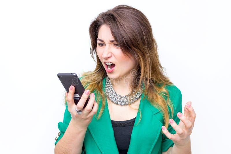 Vrouw het dragen in groen jasje schreeuwt in woede aan haar telefoon, vrouwenschreeuwen in de mobiele telefoon royalty-vrije stock foto's