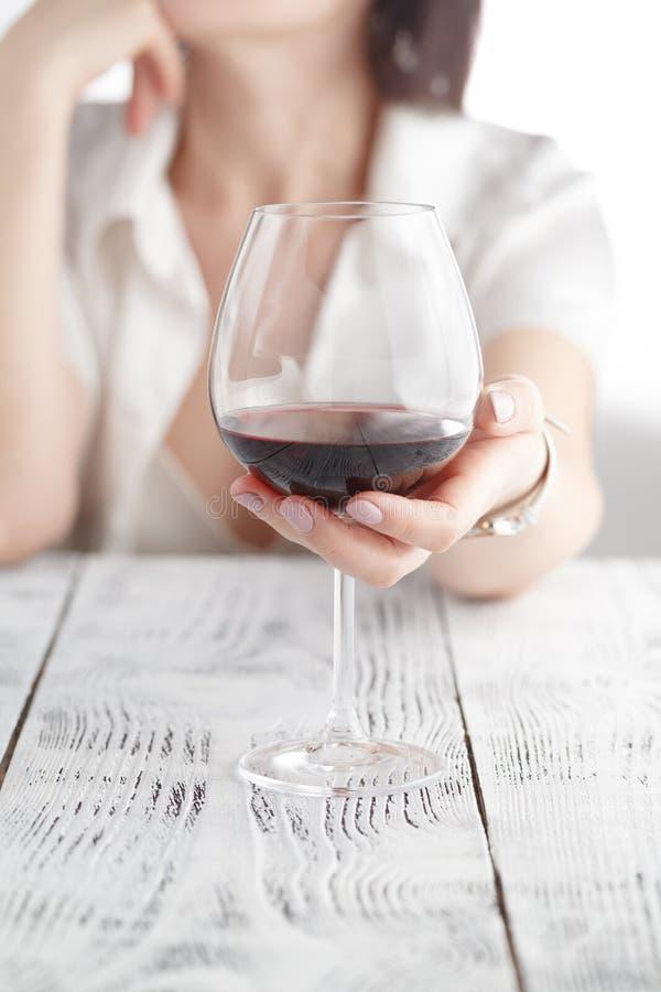 Vrouw het drinken alcohol op witte achtergrond Nadruk op wijnglas stock afbeelding