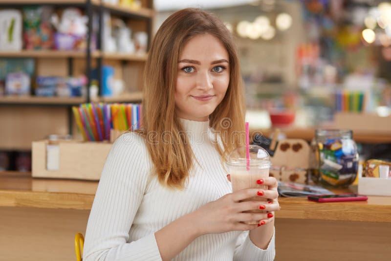 Vrouw het drinken cocktail bij bar Mooi meisje met blond haar, in wit toevallig overhemd met rode modieuze manicure Jonge aanbidd royalty-vrije stock afbeeldingen