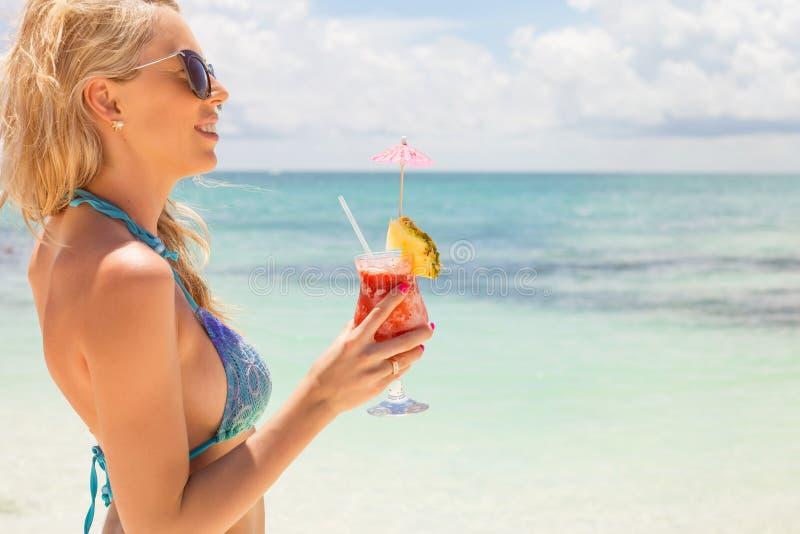 Vrouw het drinken de cocktail van aardbeimargarita op het strand stock afbeelding
