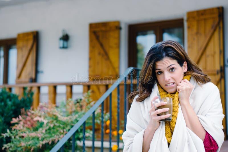 Vrouw het drinken koffie buiten huis bij het bevriezen van de koude herfst royalty-vrije stock afbeelding