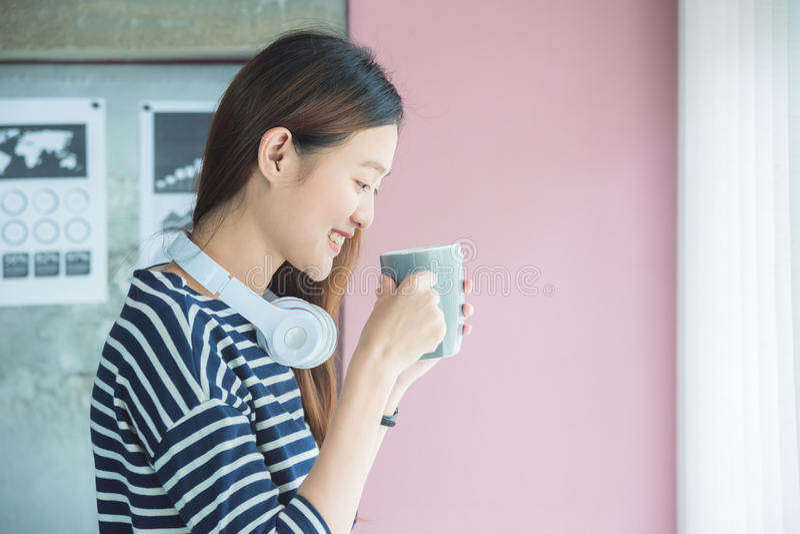 Vrouw het drinken koffie in bureau en glimlach royalty-vrije stock afbeelding