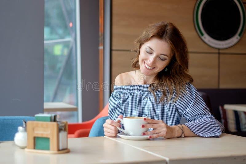 Vrouw het drinken koffie in de ochtend bij restaurant stock afbeeldingen
