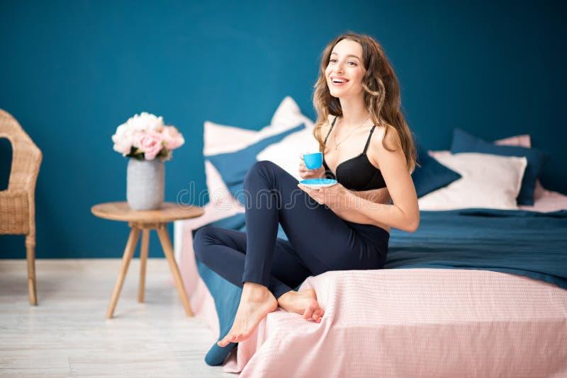 Vrouw het drinken koffie in de slaapkamer royalty-vrije stock foto's