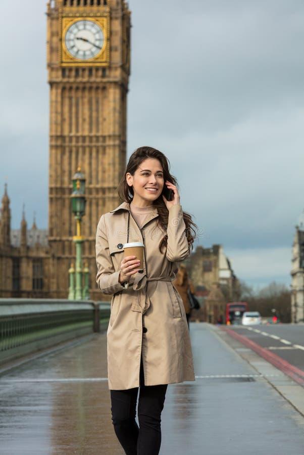 Vrouw het Drinken Koffie die op Celtelefoon spreken, Big Ben, Londen stock foto's