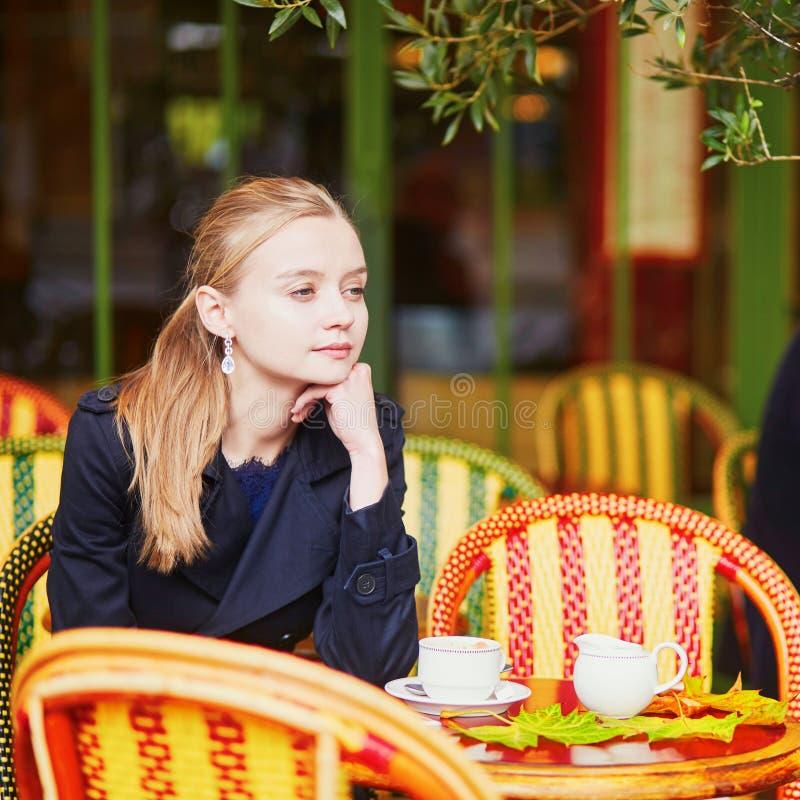 Vrouw het drinken koffie en het eten van heerlijk vers croissant in Parijse openluchtkoffie royalty-vrije stock fotografie